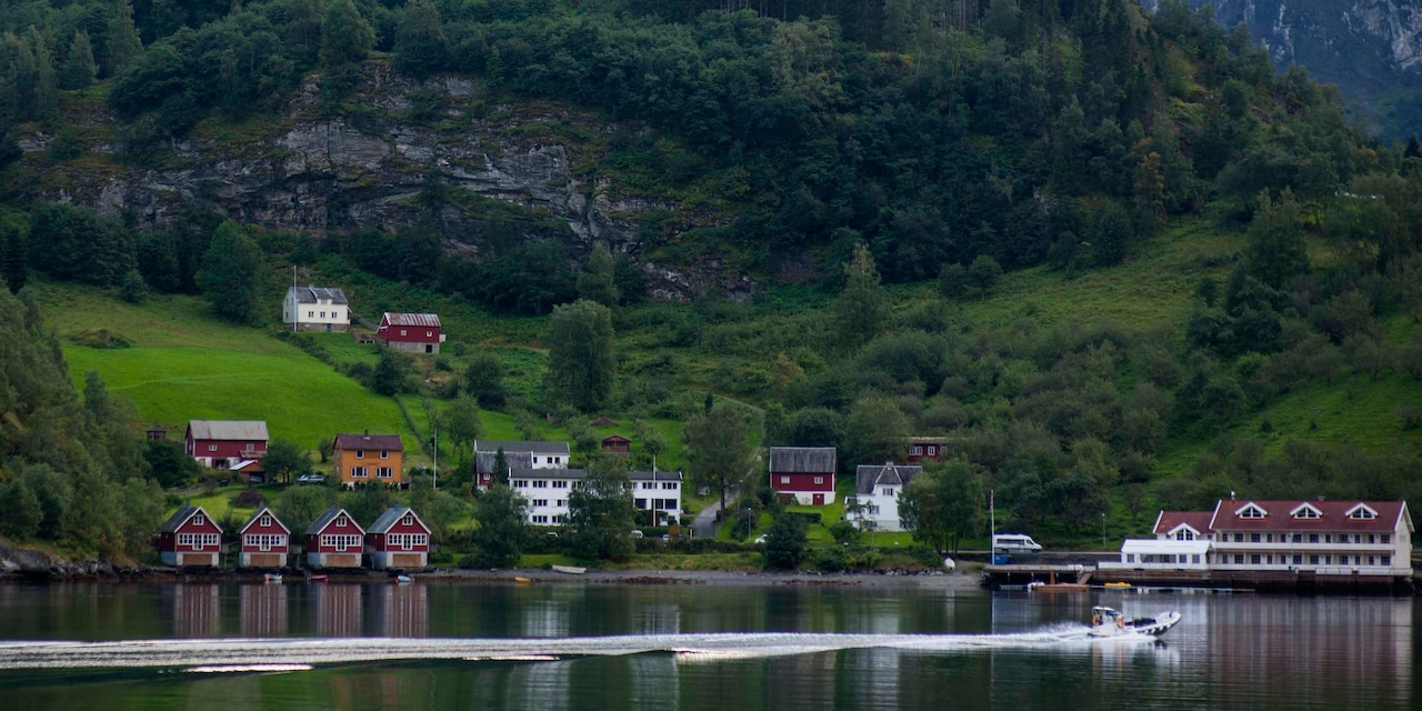 A motorboat passes a lakeside village with houses extending up the mountainside