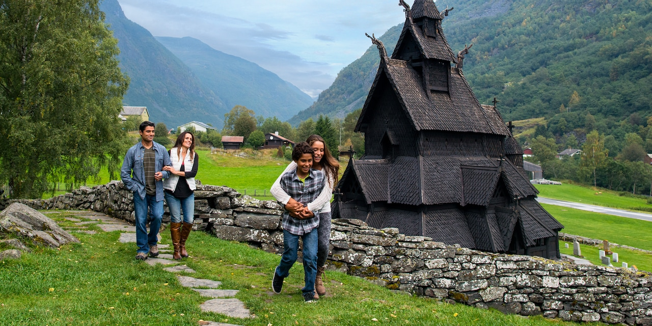 A family of 4 walks along a path near a stave church in a pastoral valley surrounded by mountains