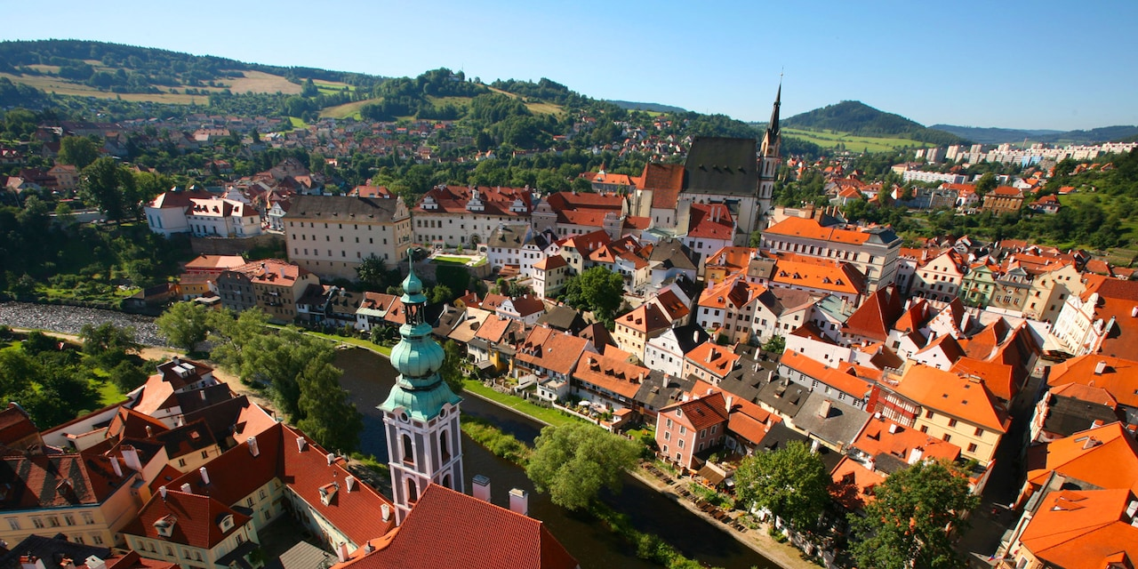 A bird's eye view of the rooftops, spires and rolling hills of Prague