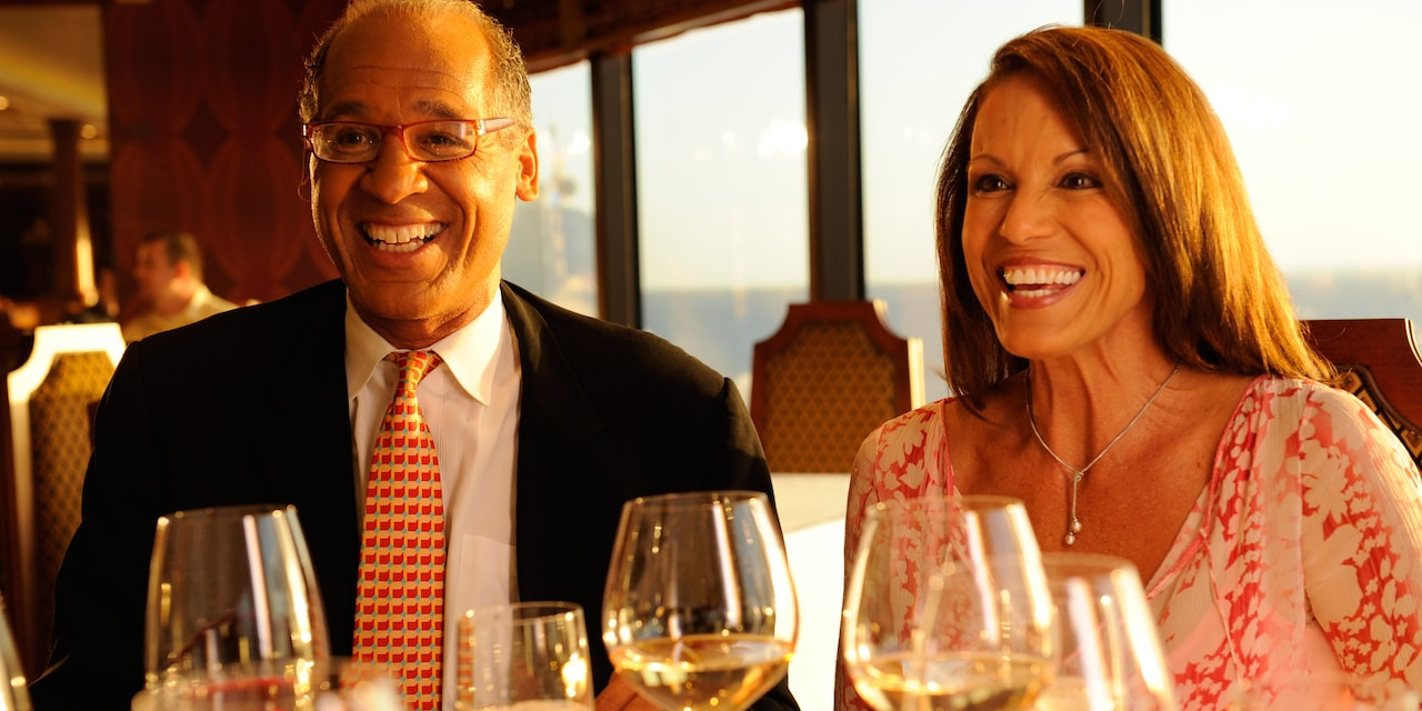 A man in a jacket and tie sits next to a woman in a dress and necklace at a table with several wine glasses