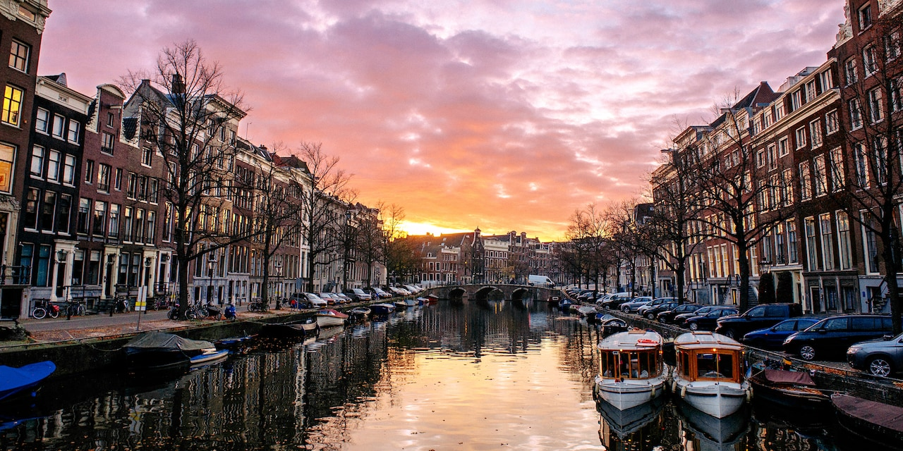 A canal lined with boats and quaint buildings on shore at sunset