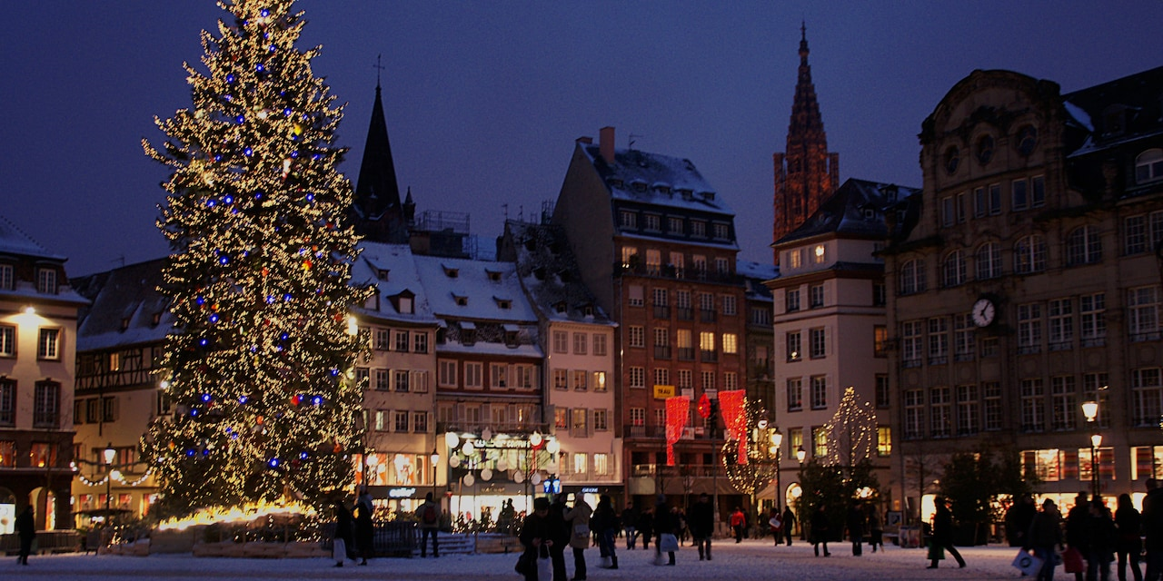 At night, lights twinkle on a tall Christmas tree in a square with pedestrians and quaint shops