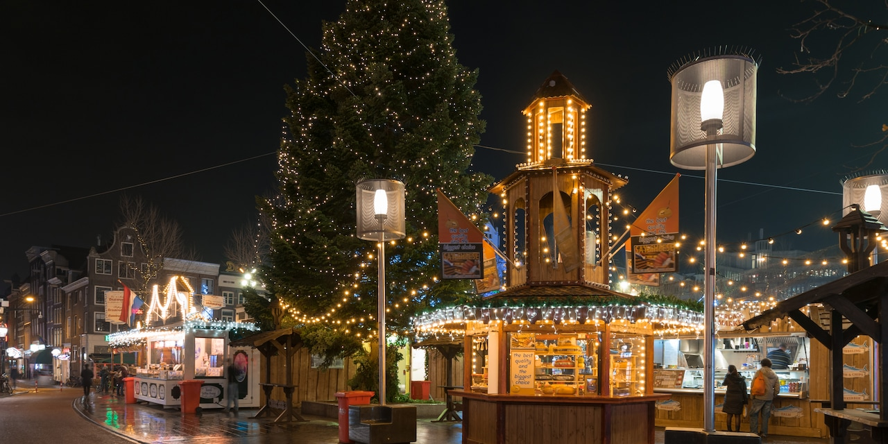 A Christmas Market at night, with twinkling lights around wooden booths and a tall Christmas tree