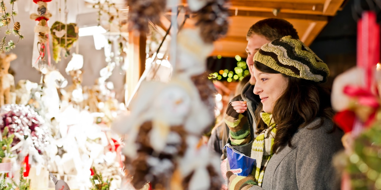 A couple admires a display of hanging Christmas ornaments