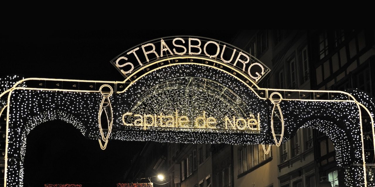 A sign made of lights on a decorated entry gate read