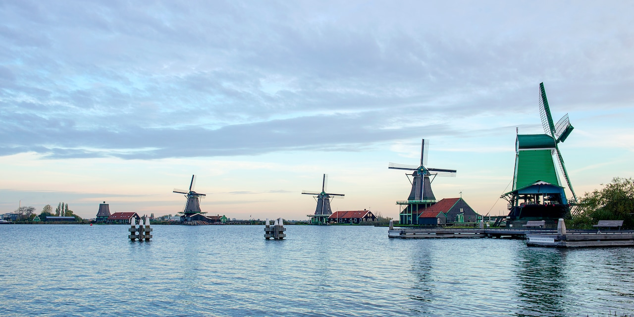 Iconic Dutch windmills along a river with clouds overhead
