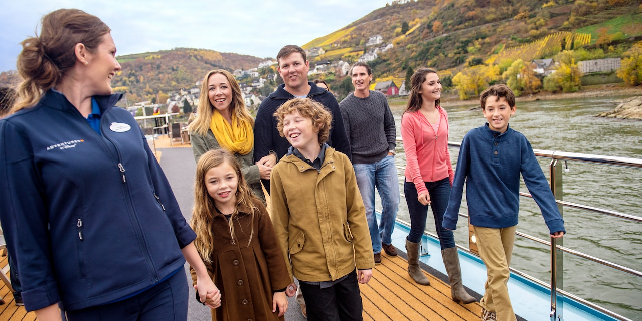 An Adventure Guide leads a family for a walk onboard the deck of a ship that's cruising down a river