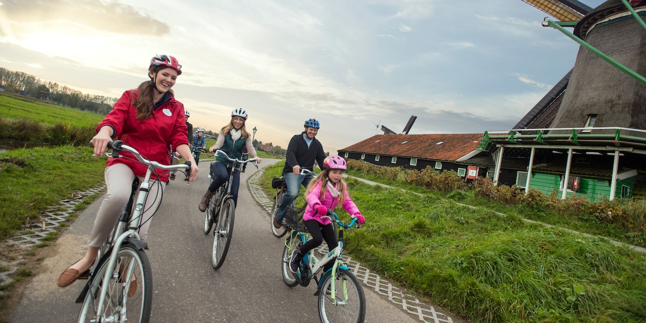 An Adventure Guide and a family of 4 bike along a path next to classic windmills