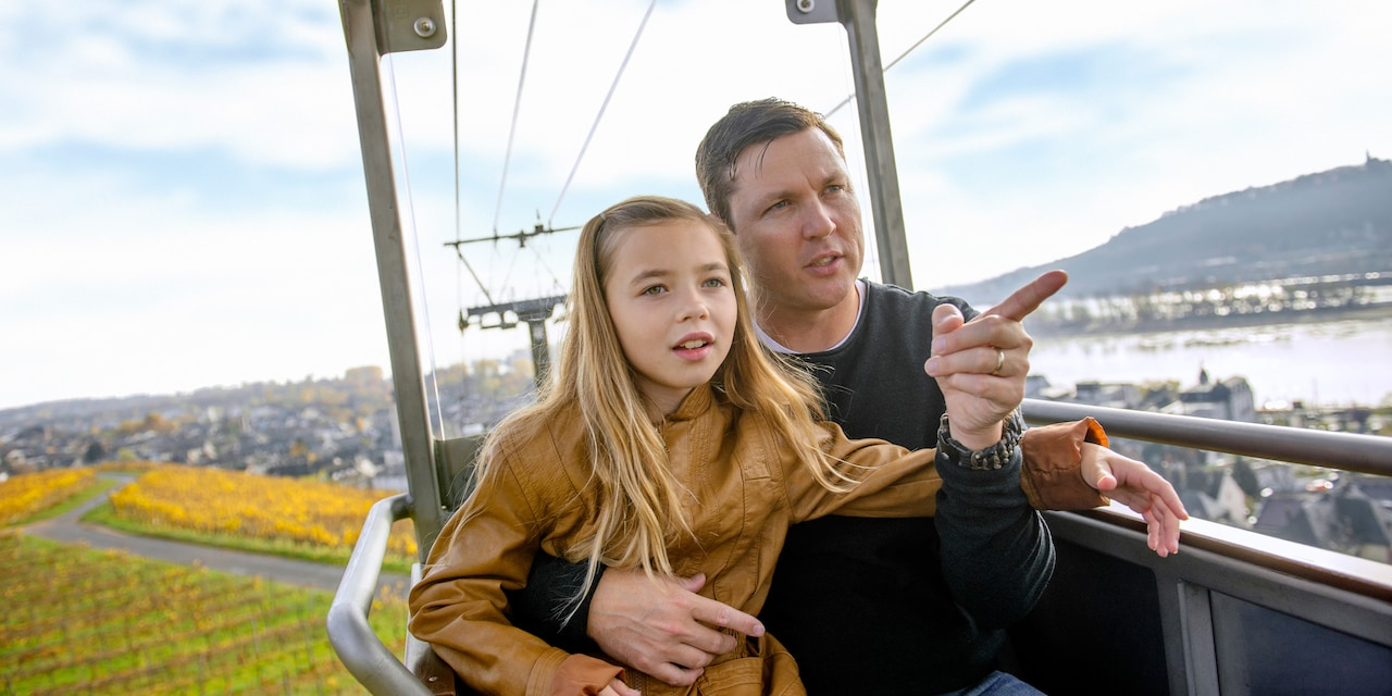 A father and daughter ride an aerial gondola up a slope