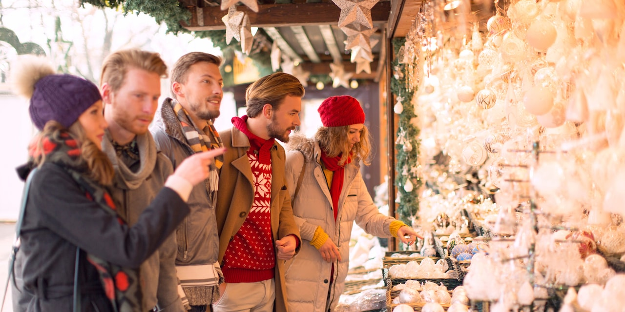 Three men and 2 women look at delicate ornaments at a Christmas Market