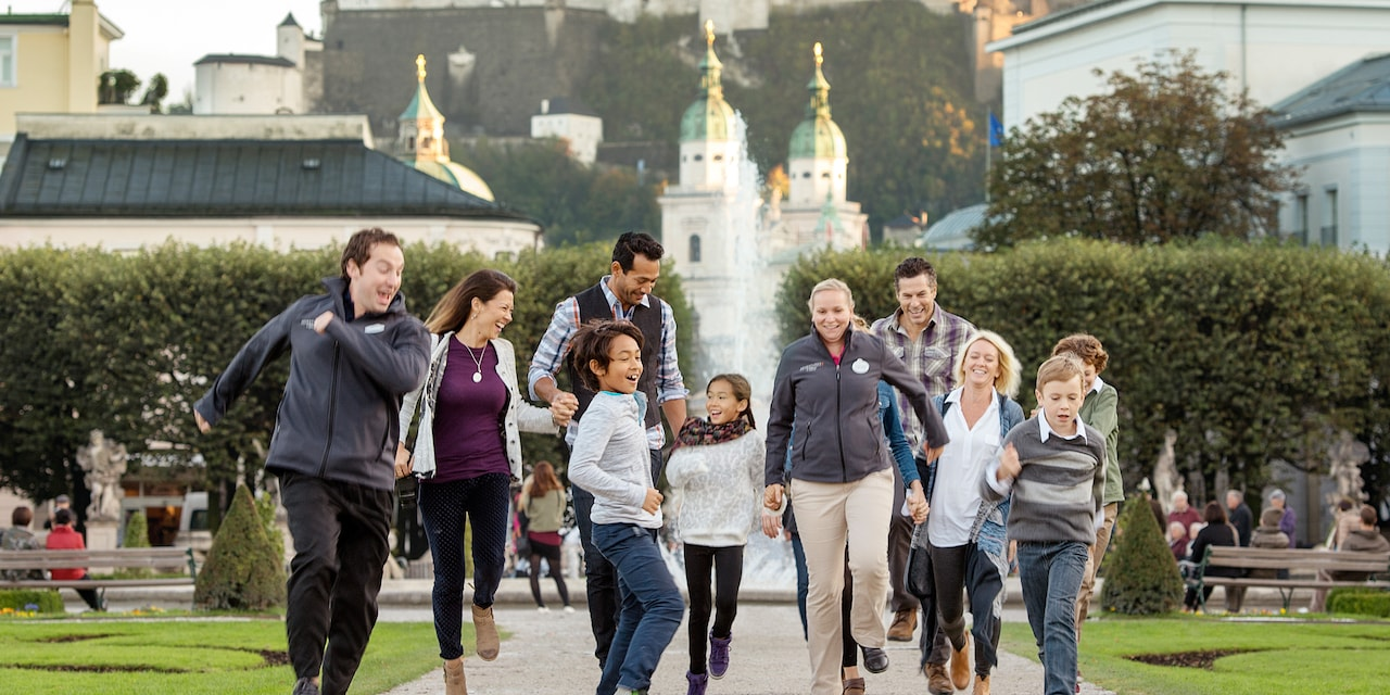 Two families happily stroll down a path by a fountain near historic buildings