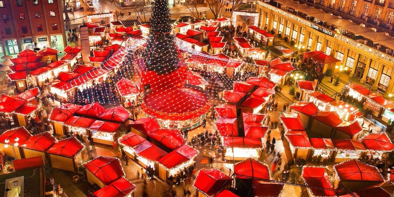 Tented roofs of shops surround a Christmas tree outside a hotel at a Christmas market