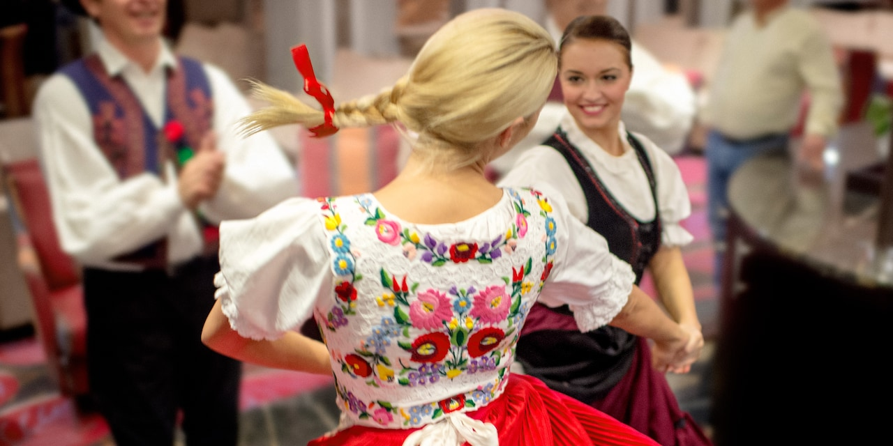 Two women and a man dance a folkdance wearing traditional embroidered German costumes