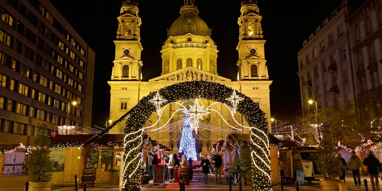 A Christmas Market in front of a church, with a lit Christmas tree and a holly archway