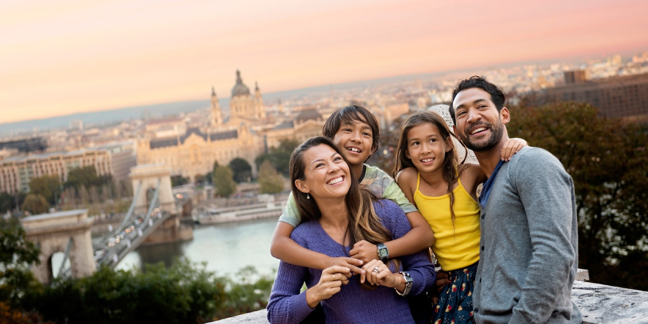 A family of 4 above a city look around with a sense of excitement