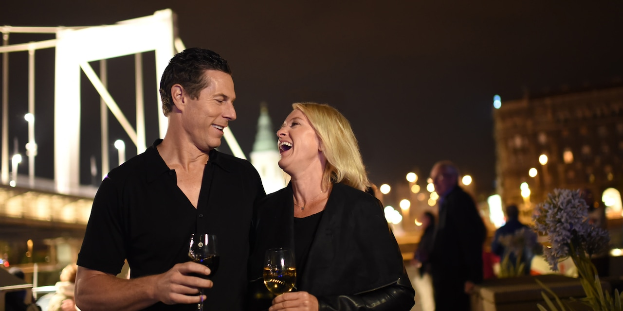 A laughing couple drinks wine