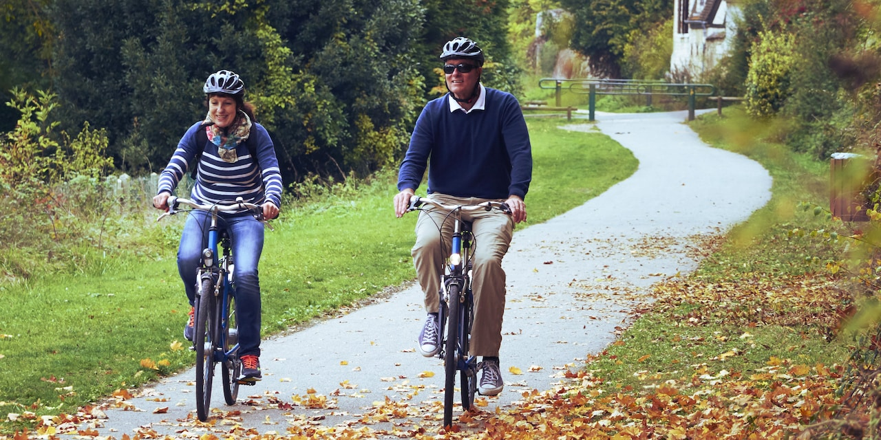 A couple ride bikes along a bike trail in the town of Les Andelys