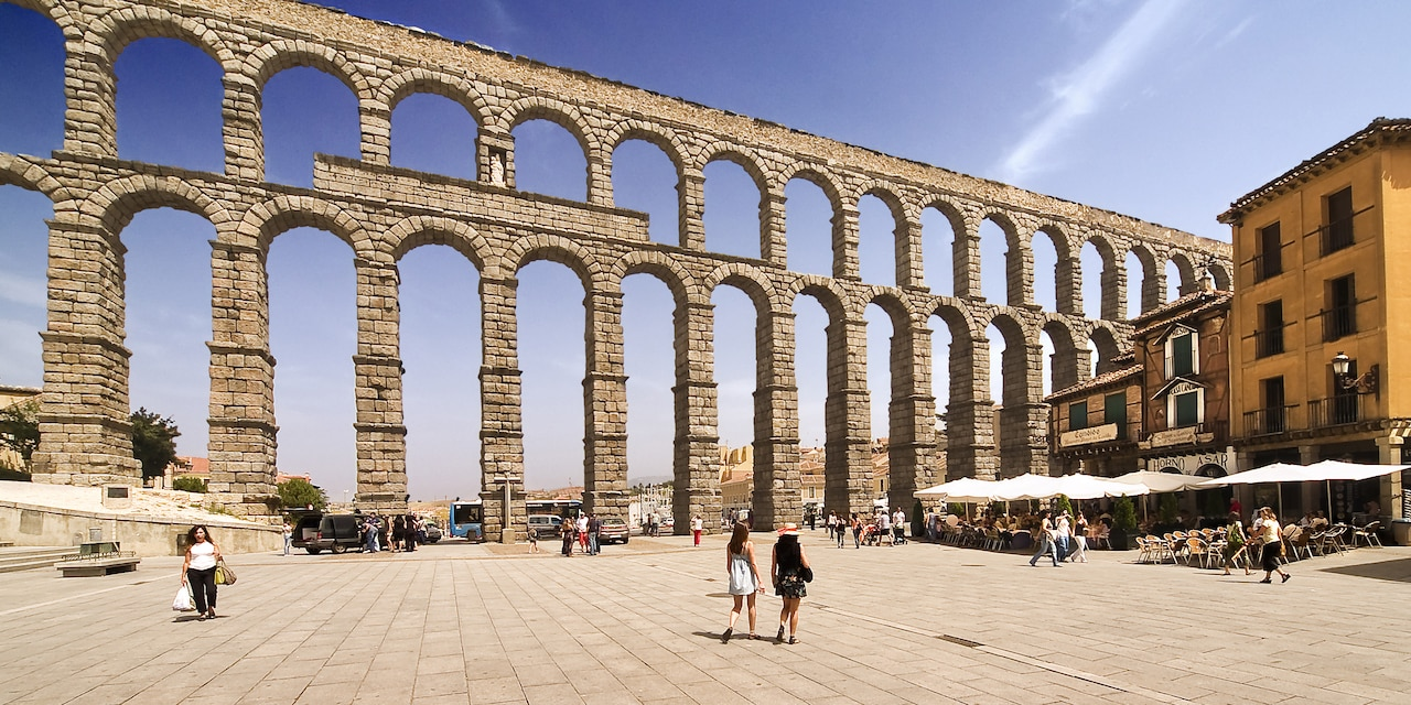 Tourists sit under umbrellas in a café next to the 2,000 year old Roman Aqueduct of Segovia