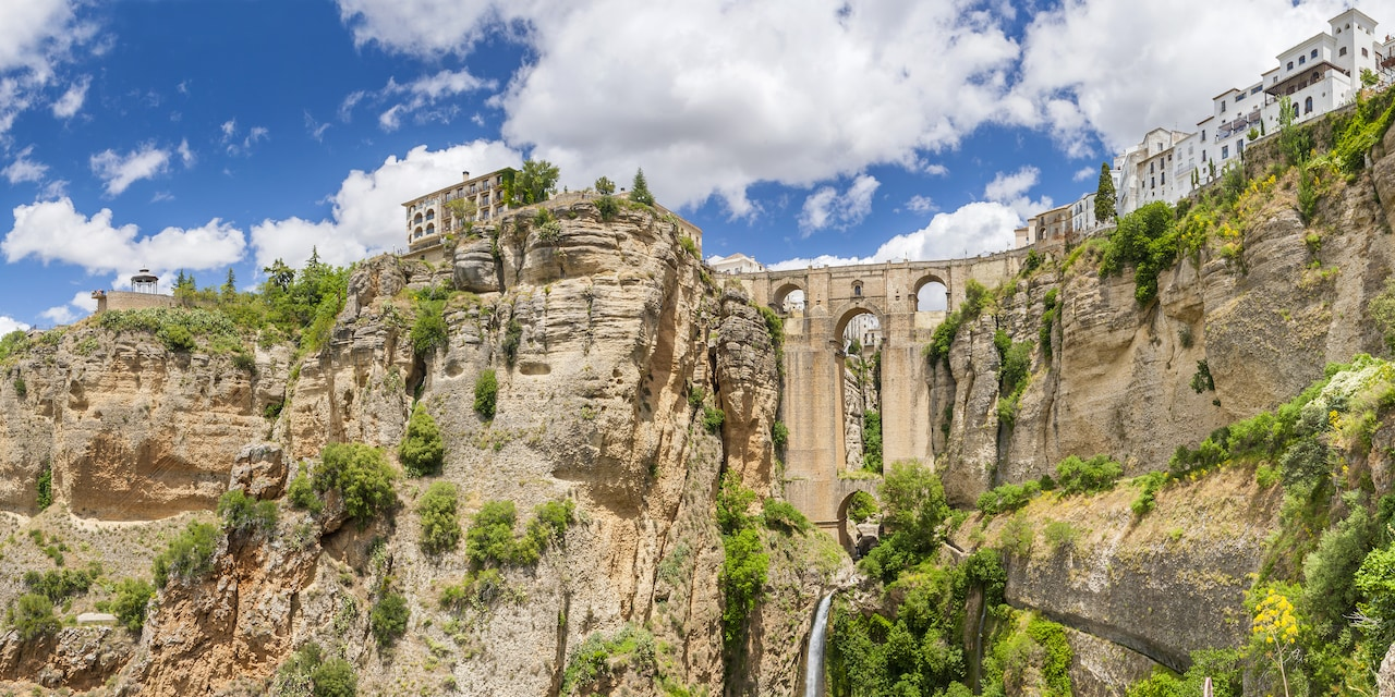 The Puente Nuevo bridge spans the gorge between 2 steep cliffs
