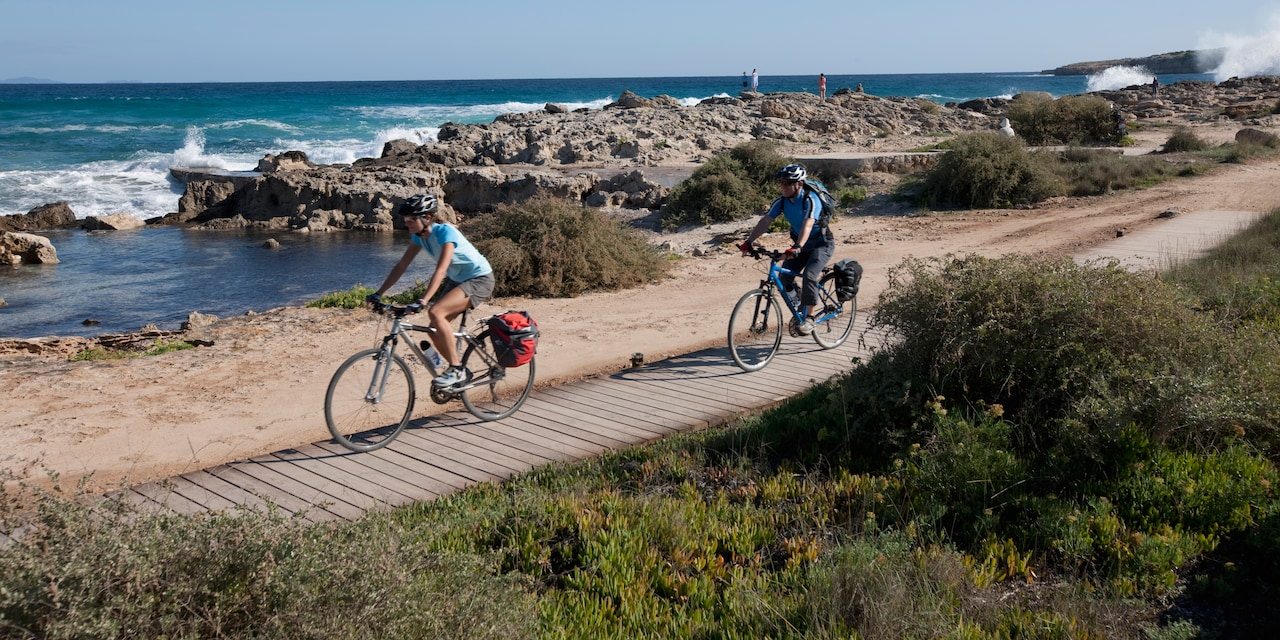 Two bicyclists ride their bikes on a boardwalk near a rocky coast