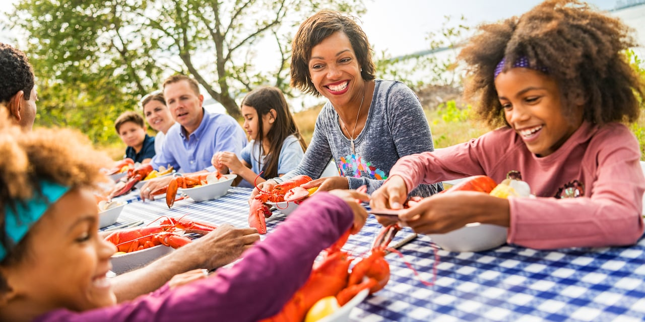 A group of people enjoy lobster and crawfish at a long picnic table