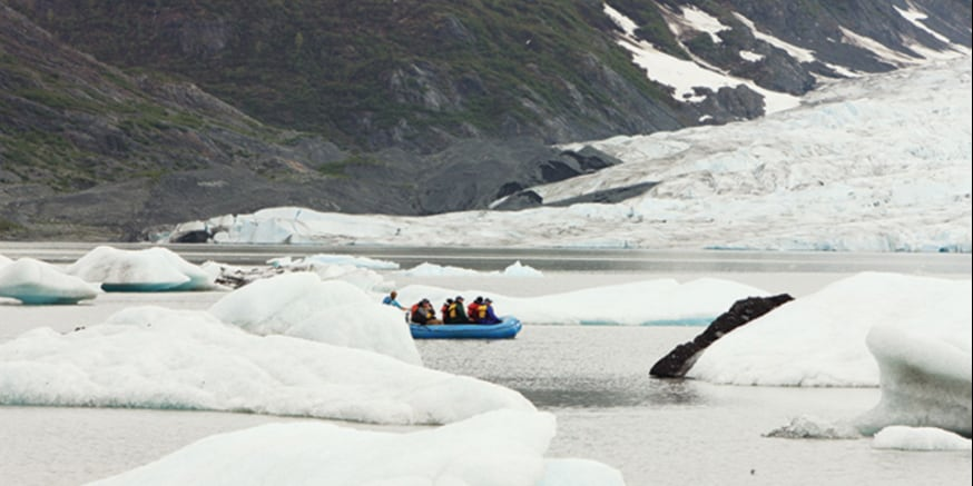 A raft filled with people drifts through glacier-filled waters