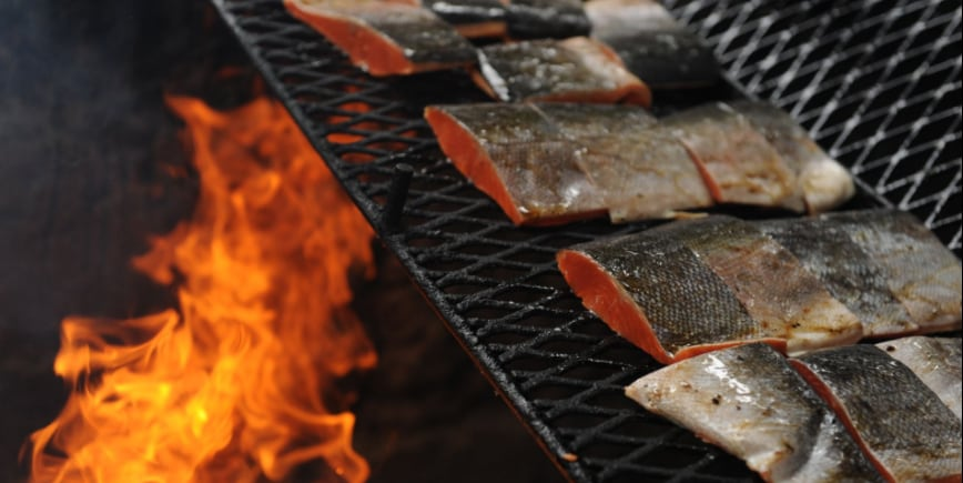 Pieces of salmon cook on a grill over a fire