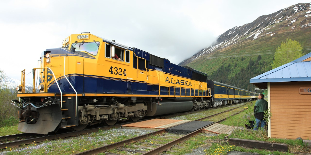 An Alaskan train approaches a railroad station in the countryside