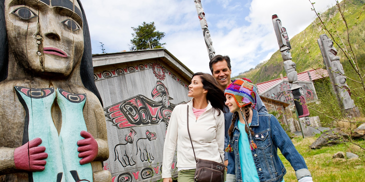 Mom, dad and daughter view an outdoor exhibit of native Alaskan artwork and totem poles