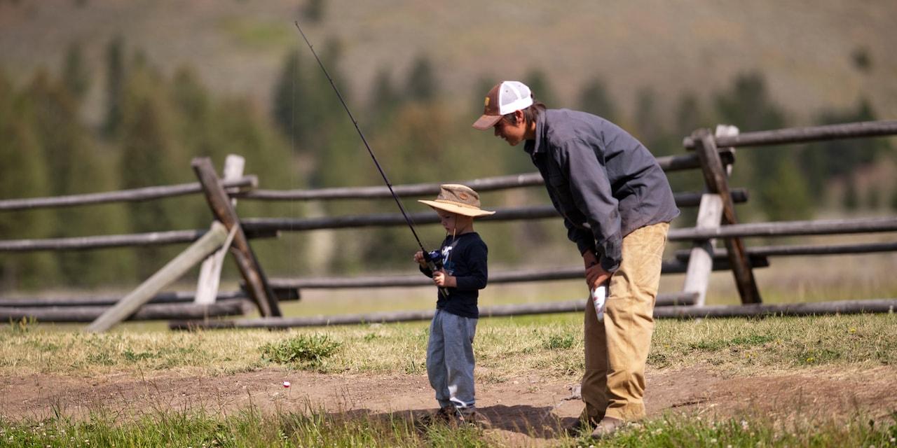 A man watches a boy fishing