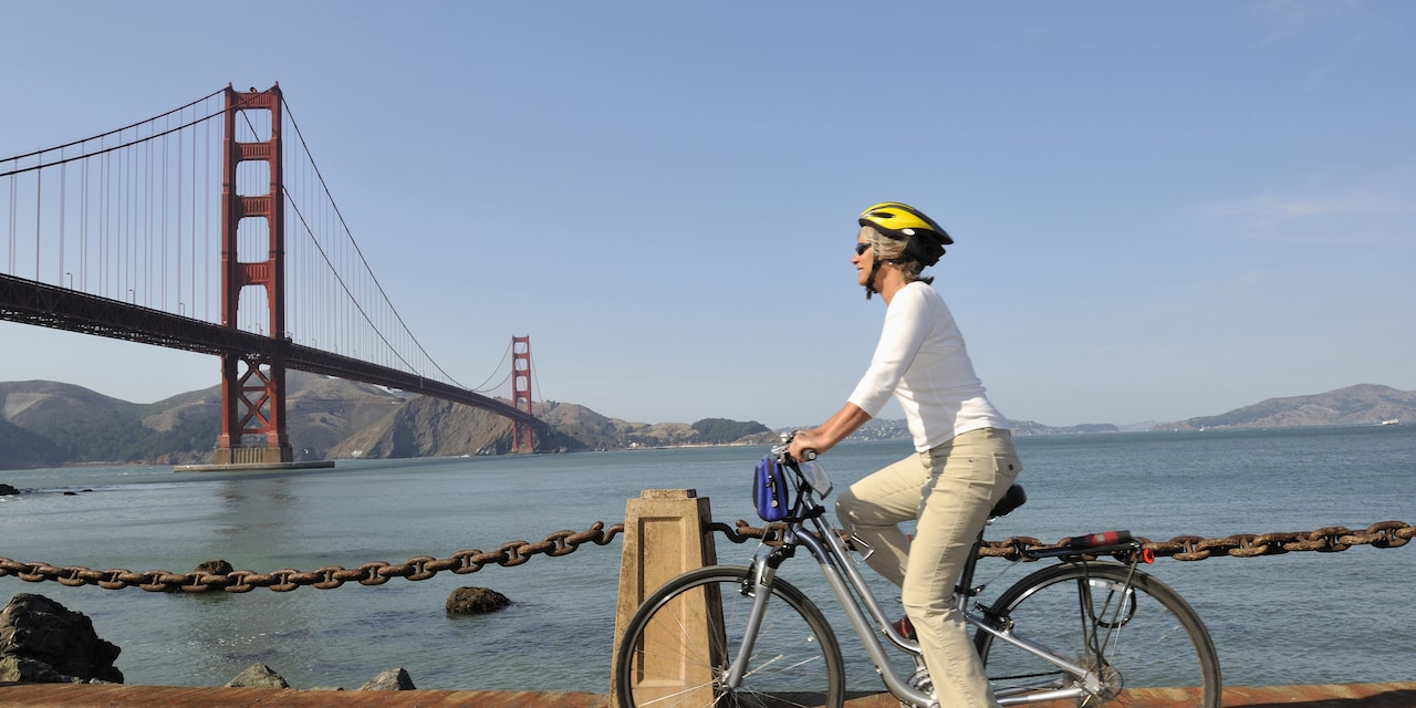 A woman rides a bike alongside San Francisco Bay near the Golden Gate Bridge