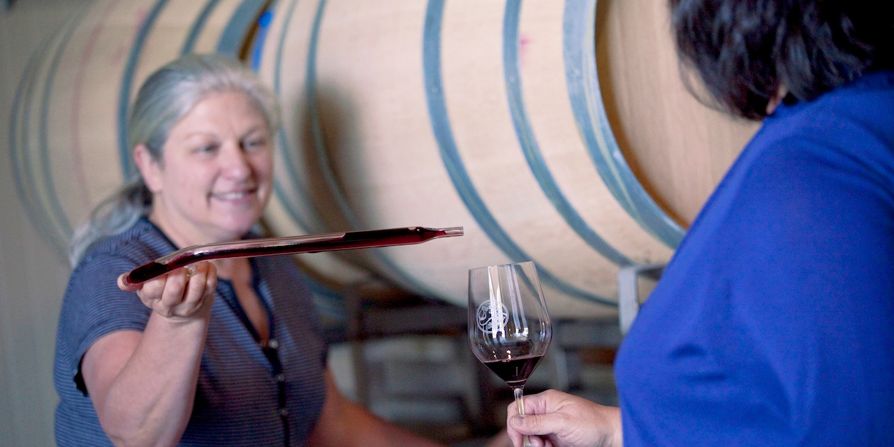 A female vintner pours wine into a woman's wine glass