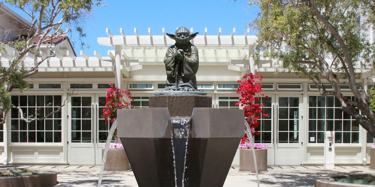 The exterior of Lucasfilm headquarters with a statue of Yoda standing guard at the entrance