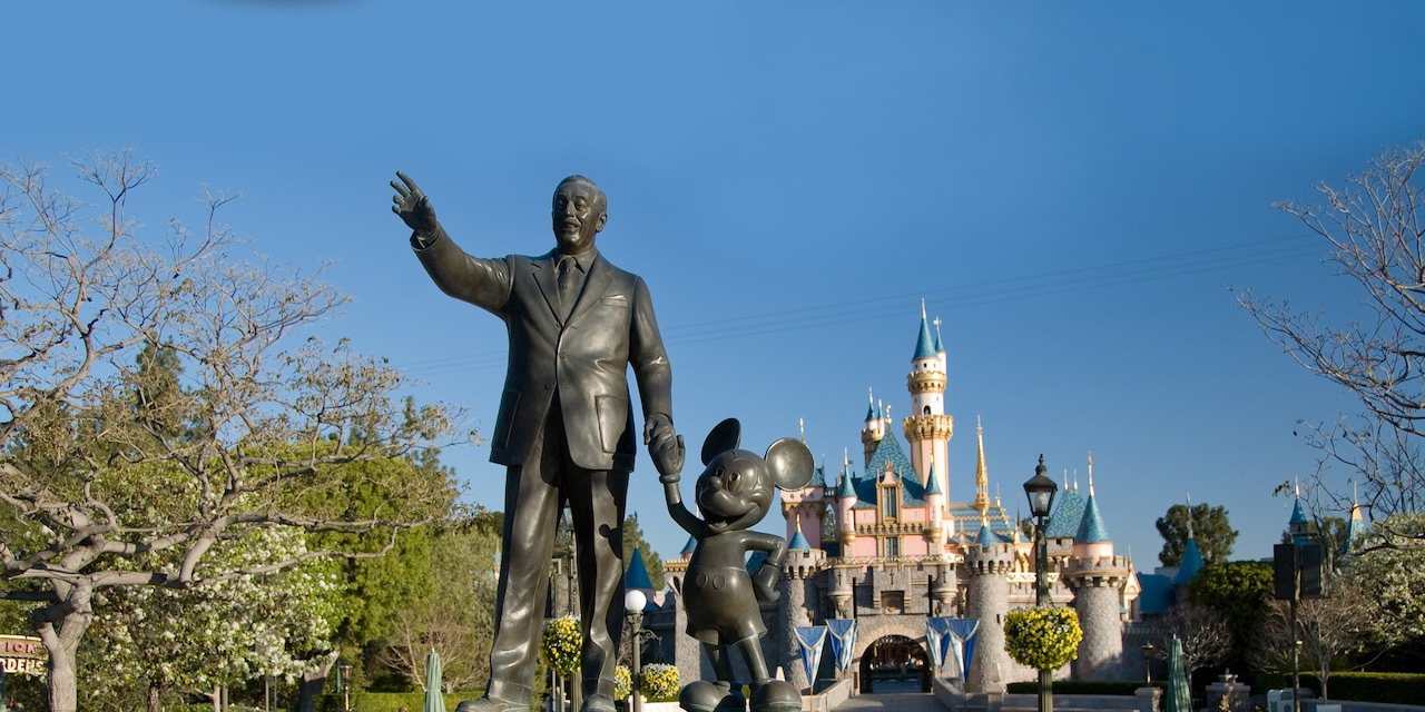 "The Disneyland Park ""Partners"" statue featuring Walt Disney and Mickey Mouse in a bed of tulips with Sleeping Beauty Castle in the background"