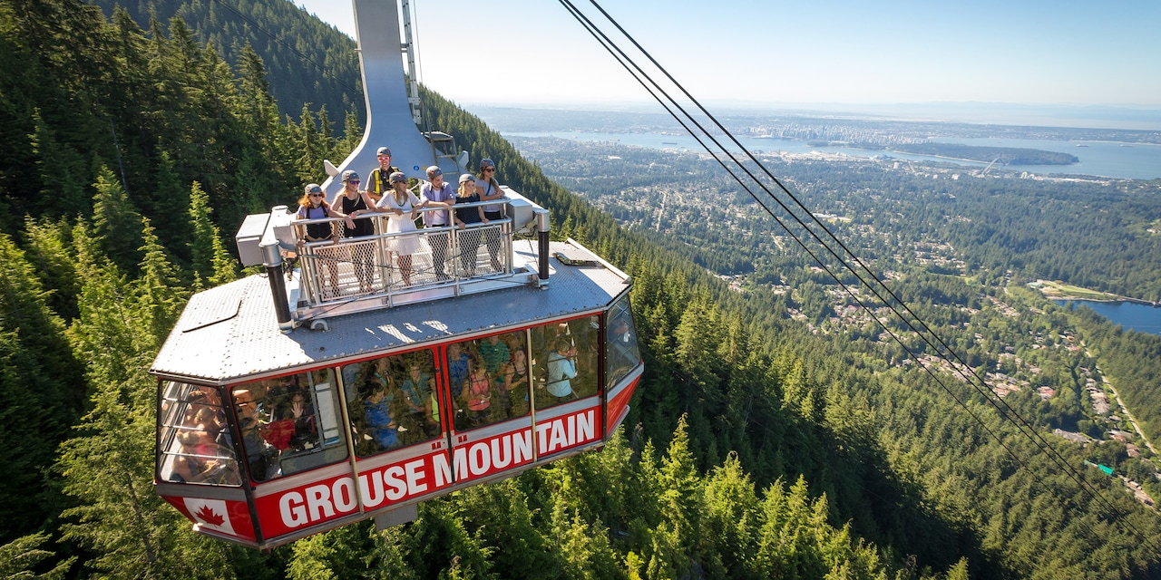 People ride the Grouse Mountain gondola above the trees