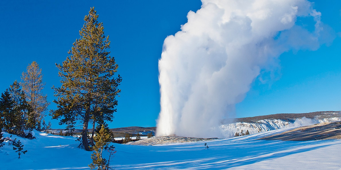 On a snowy terrain, a geyser sprays plumes of steam in the air