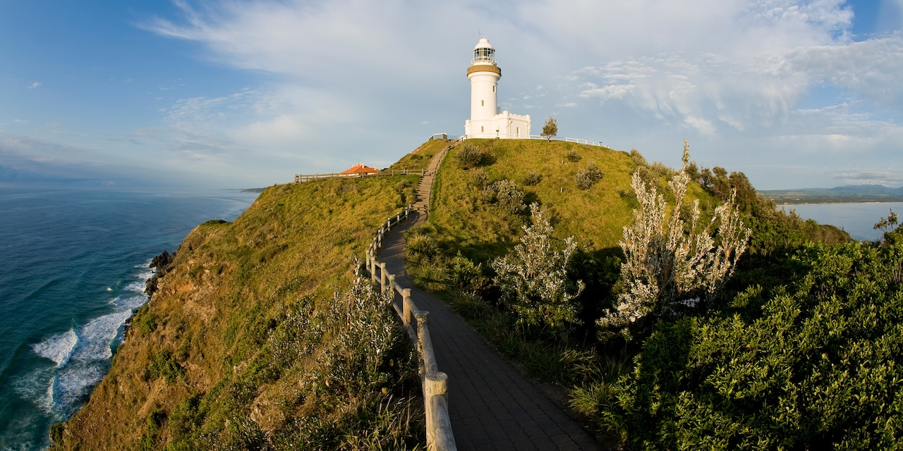 A lighthouse atop a hill surrounded by the ocean