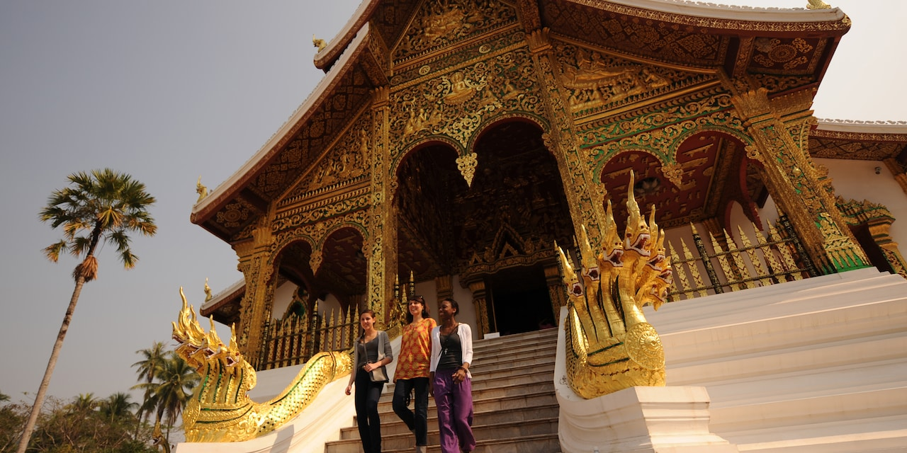 3 teenage girls walk down the steps of an ornate building
