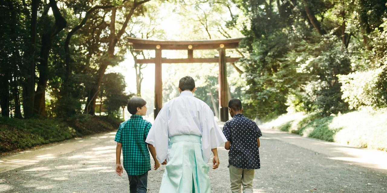 Two boys and a monk walk down a path towards a tojii gate at Meiji Shrine