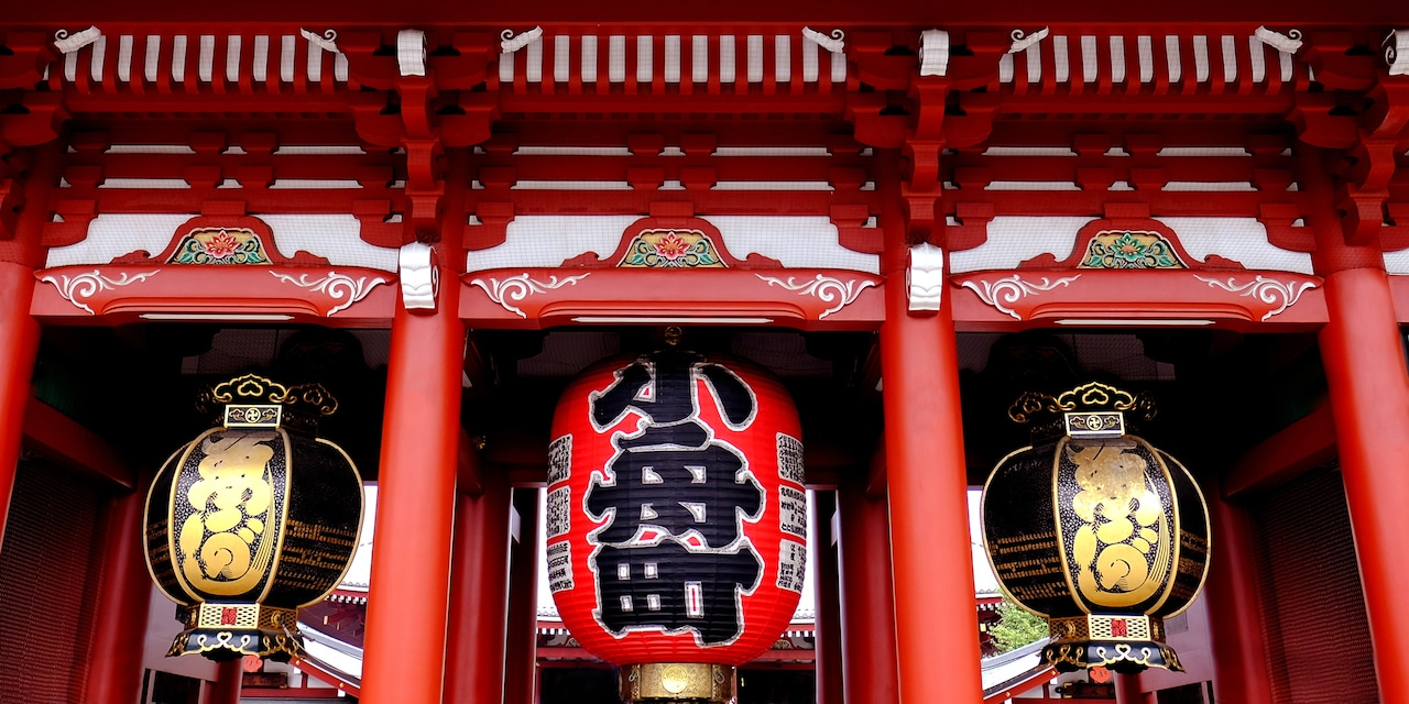 A large, red lantern hangs between to smaller lanterns outside a temple