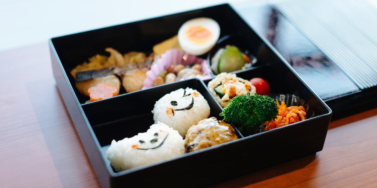 A Japanese bento box filled with various food, including rice balls with seaweed faces