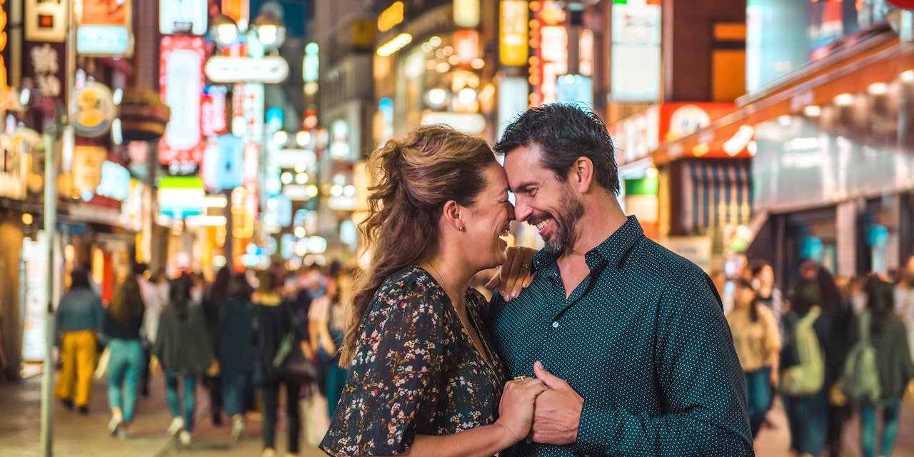 A couple hold hands while sharing a romantic moment on a neon-lit Tokyo street at night