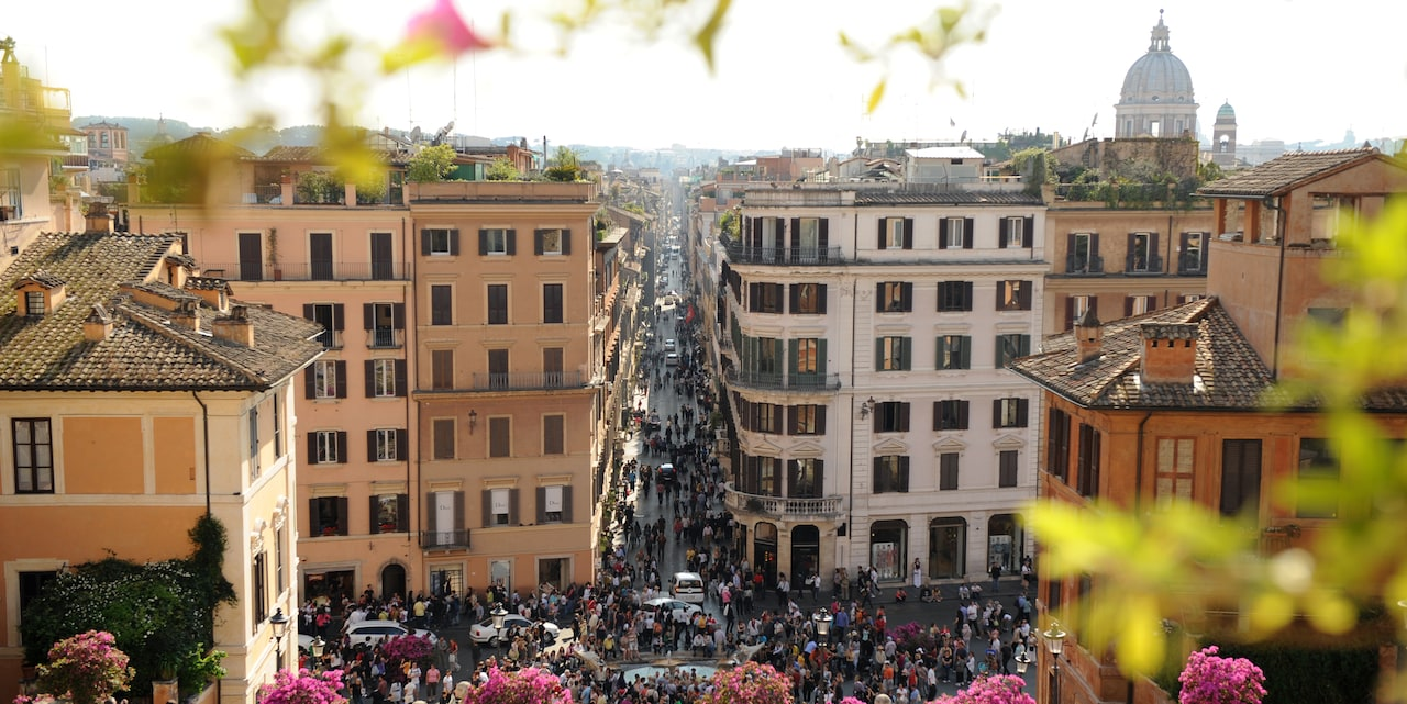 A rooftop view of a crowed street in Rome with a domed church in the distance