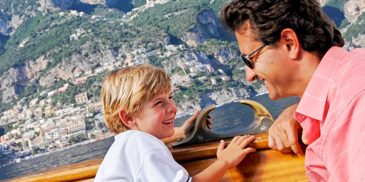 A father and son share a laugh while cruising on a boat along the Italian coast