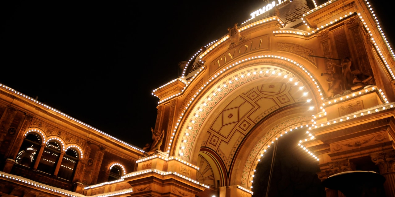 The arched entrance of Tivoli Gardens at night