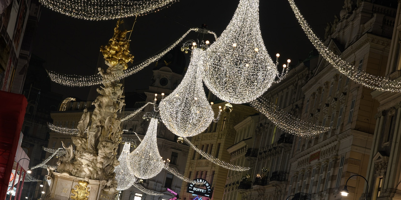 Hanging holiday lights span across a Vienna street with an ornate fountain