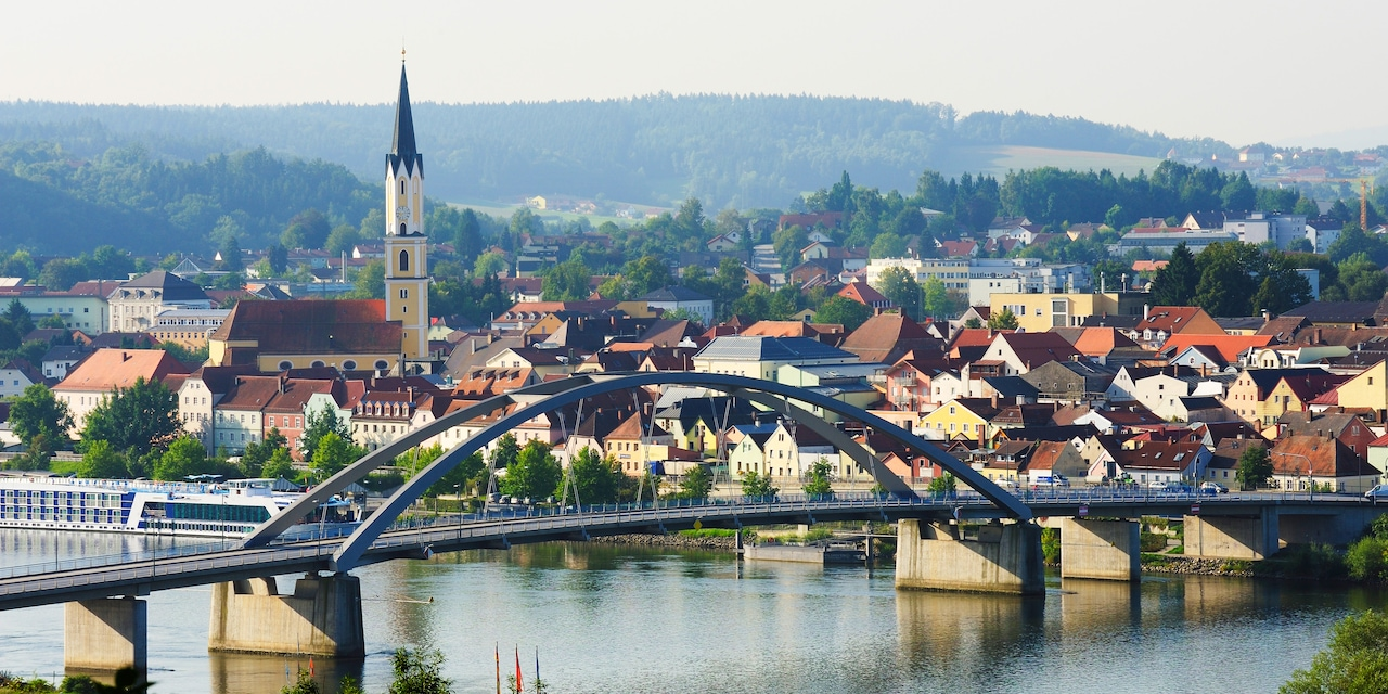 A bridge over a river and a quaint town with a steepled church on one side
