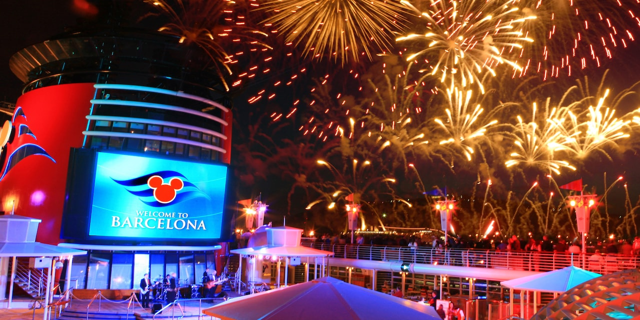 Fireworks over the deck of the Disney Magic Ship and a sign reading 'Welcome to Barcelona'