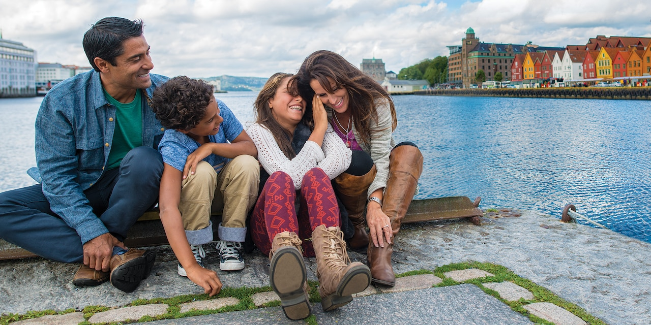 A Family Of 4 With Older Children Sit On Dock Across Fjord From