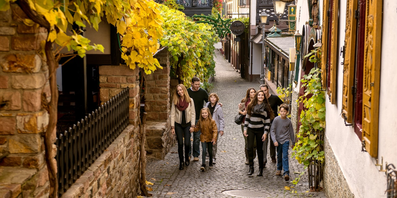 Two families walk up a cobblestone alley flanked by charming buildings
